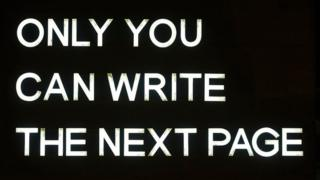 A-strip-light-sign-in-white-reads-only-you-can-write-the-next-page.