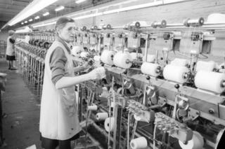 Woman working at a thread spinning machine