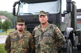 Corporal Christopher Seidel (L) and Staff sergeant Friedemann Frischko (R) stand in front of their army truck
