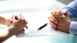 2 pairs of hands folded over signed legal document