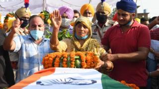 Cachemira Kaur (C) gesticula después de colocar las coronas de flores en el ataúd de su hijo y soldado Satnam Singh.