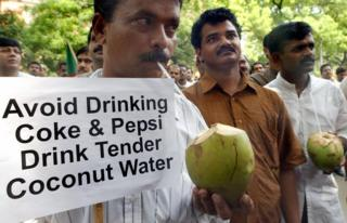 Activists of the Indian federal Democratic Party drink coconut water during a demonstration against against cola giants Pepsi and Coke in New Delhi, 21 August 2003.