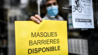 A pharmacist in France puts up a sign reading 'protective facemasks are available'