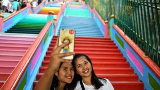 Two women take selfies at the colourful staircase to the Batu Caves complex