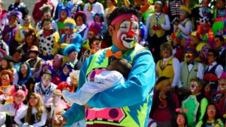 A clown holding a baby at a clown convention
