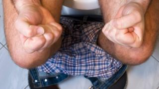 A man sat on the loo, clenching his fists