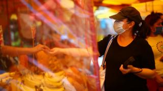 A woman buys at a local market as it reopens in Mexico City
