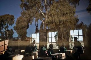 in_pictures Secondary students sit in a classroom. The trees outside are reflected on the window pane.