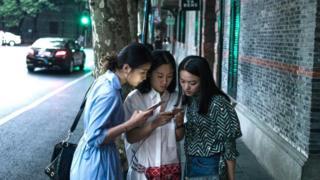 Chinesas observam telefone celular