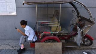 Woman on auto-rickshaw staring at phone