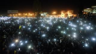 A crowd using their mobile phone lights at a sit-in at the military HQ in Khartoum, Sudan - Sunday 7 April 2019