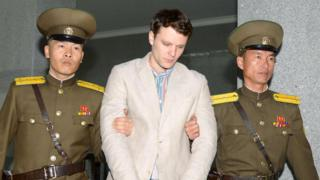 Otto Frederick Warmbier, flanked by two North Korean guards