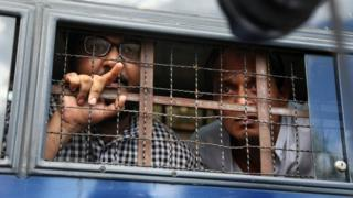 Two men look out of a vehicle whose window is protected with a steel wire barricade
