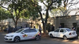 Police cars wey park for front of Gupta family house
