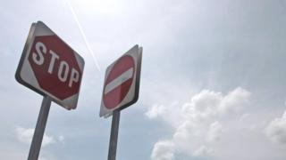 Дорожные знаки на фоне облаков