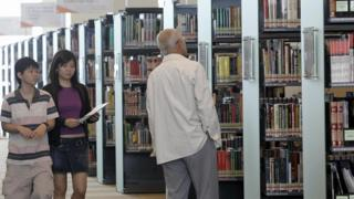 People walk in a library in Singpore