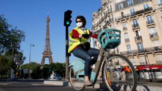 A woman wearing a face mask rides her bicycle in Paris, with the Eiffel Tower captured behind her