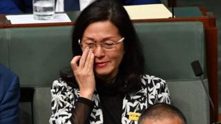Gladys Liu wipes away a tear while sitting in Australia's parliament