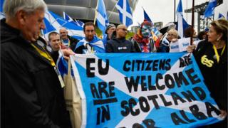 Independence supporters hold up a banner stating that EU citizens are welcome in Scotland as they take part in a rally outside the Scottish National Party conference on October 15, 2016 in Glasgow,