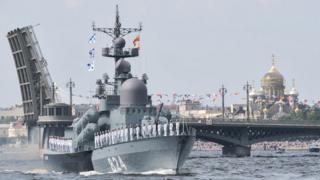 """Большой ракетный катер """"Моршанск"""" на фоне разведенного Благовещенского моста в Петербурге."""
