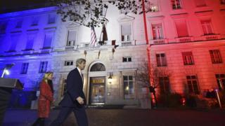 John Kerry and US Ambassador to France Jane D Hartley outside US embassy in Paris illuminated with the colours of French national flag. 16 Nov 2015