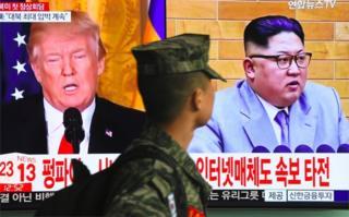 Un soldado surcoreano camina frente a una pantalla que muestra imágenes de Donald Trump y Kim Jong-un.