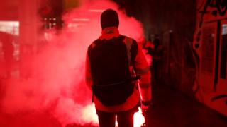 A French SNCF railway worker on strike holds a flare as he walks through Gare du Nord railway station before a demonstration against the French government's pension reform plans in Paris as part of a day of national strike and protests in France, 5 December, 2019.