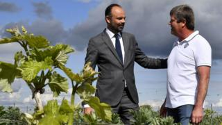French Prime Minister Edouard Philippe (L) speaks with winegrower Christophe Charrier who manages a winery engaged in pesticide and glyphosate reduction in Val des Vignes near Angouleme, western France, on May 3, 2019,