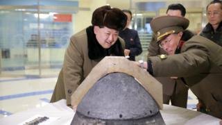 North Korean leader Kim Jong-un looks at a rocket warhead tip (undated image)