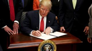 President Donald Trump signs an Executive Order to begin the roll-back Obama-era environmental regulations on 28 February 2017