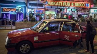 Two women getting into a taxi in front of bars and restaurants in Hong Kong