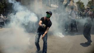 Joven en medio de gases lacrimógenos.