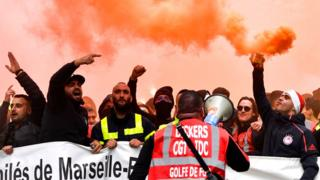 Dockers march with smoke bombs and hold a banner as they take part in a demonstration to protest against the pension overhauls, in Marseille, southern France, 5 December
