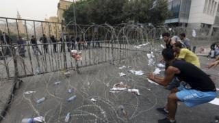 Lebanese anti-government protesters try to remove barbed wire that blocks a road leading to the parliament building on 9 September 2015