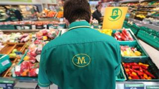 An employee works on the fresh vegetable display at a Morrisons supermarket,