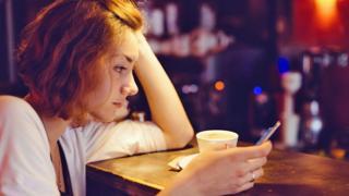 Telefonuna bakan bir kadın