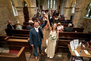 A wedding couple pose in a church
