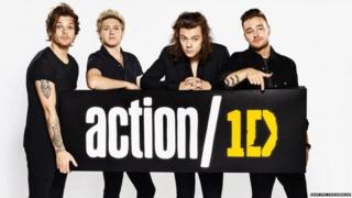 Louis, Niall, Harry and Liam from One Direction hold a sign highlighting action/1D