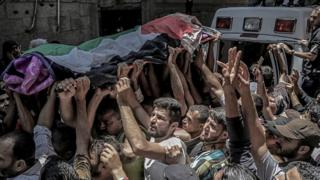 Palestinian mourners carry the body of Razan al-Najar during her funeral in Khan Younis, southern Gaza Strip, 2 June 2018