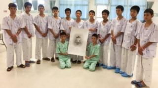 12명의 태국 소년들과 코치는 구조 중 목숨을 잃은 사만 푸난의 초상화와 함께 사진을 찍었다