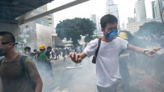 Демонстрант у масці тікає від сльозогінного газу