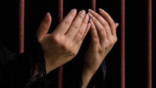 Hands behind bars