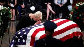 Cindy McCain leans over his casket as his body lies in state inside the US Capitol in Washington on 31 August 2018
