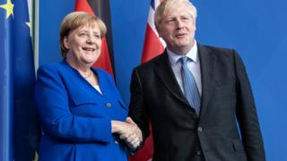Angela Merkel and Boris Johnson shake hands in Berlin