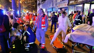 Medics attend people evacuated from the Bataclan concert hall