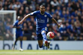 Riyad Mahrez kicking a football whilst playing a match with Leicester City