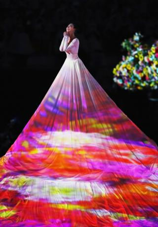 A dancer in a long white dress performs at the closing ceremony