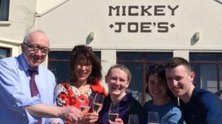 Michael Gallagher, left, celebrates with colleagues after the winning ticket was sold in his shop, Mickey Joe's Country Store in Carrigart