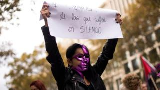 "A woman holds a placard reading ""We are the voice of those who suffer in silence"" during a demonstration under the slogan ""Together we buried the patriarchal order"" to mark the International Day for the Elimination of Violence against Women in Barcelona"