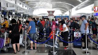 Sejumlah calon penumpang pesawat udara antre untuk lapor diri di Bandara Internasional Kualanamu, Kabupaten Deli Serdang, Sumatera Utara, Senin (14/1/2019).